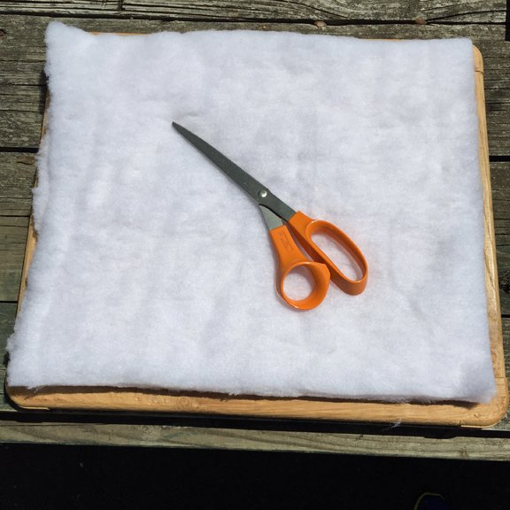 Cutting a double thickness of quilt batting to use in restoring the seat of a vintage sewing machine