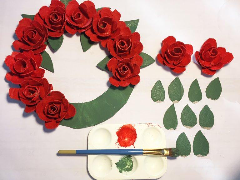 Red egg carton roses glued onto a green cardboard frams