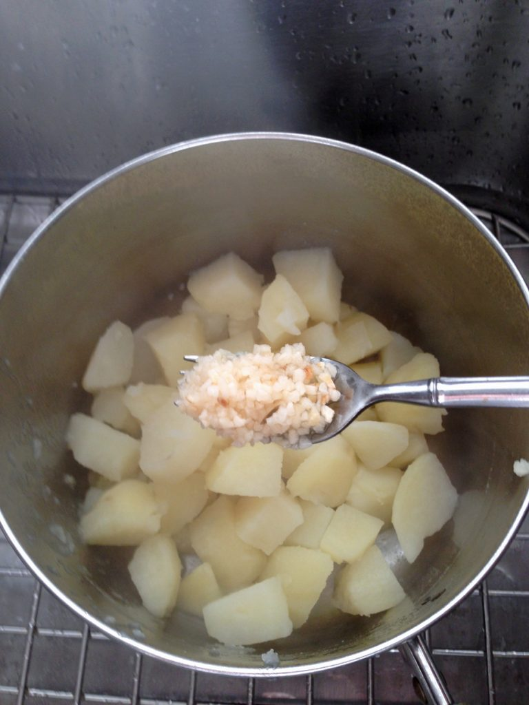 Adding minced garlic to the diced, cooked potatoes for a garlic mashed potato recipe