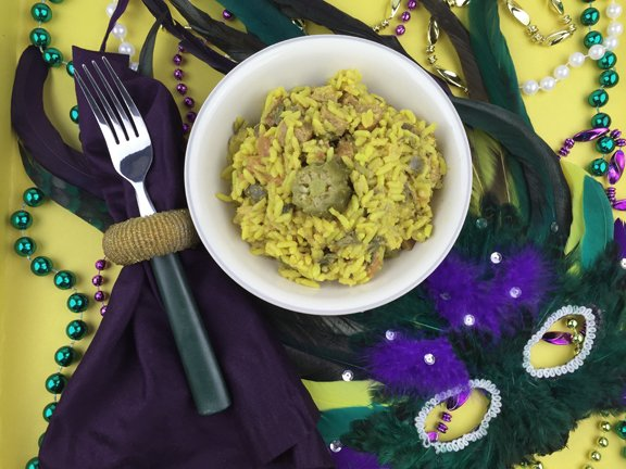 Bowl of jambalaya, Mardi Gras beads and feathered mask