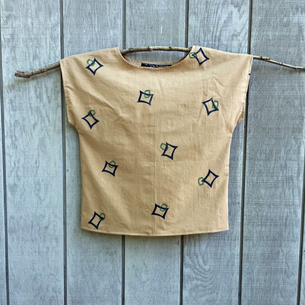 Wearable art made with a handmade tan top and custom stamp design