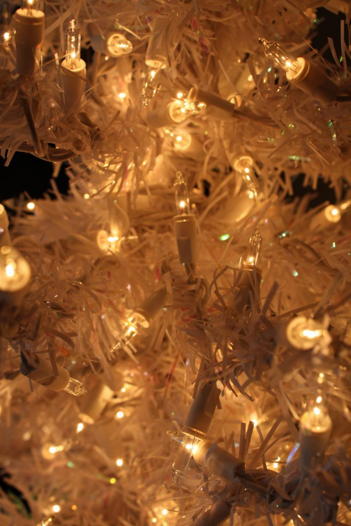 A close-up of lit white lights on a white Christmas tree