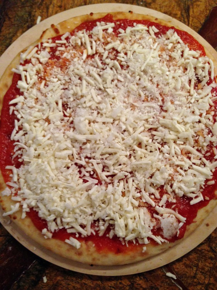Shredded mozzarella cheese on an uncooked pizza crust