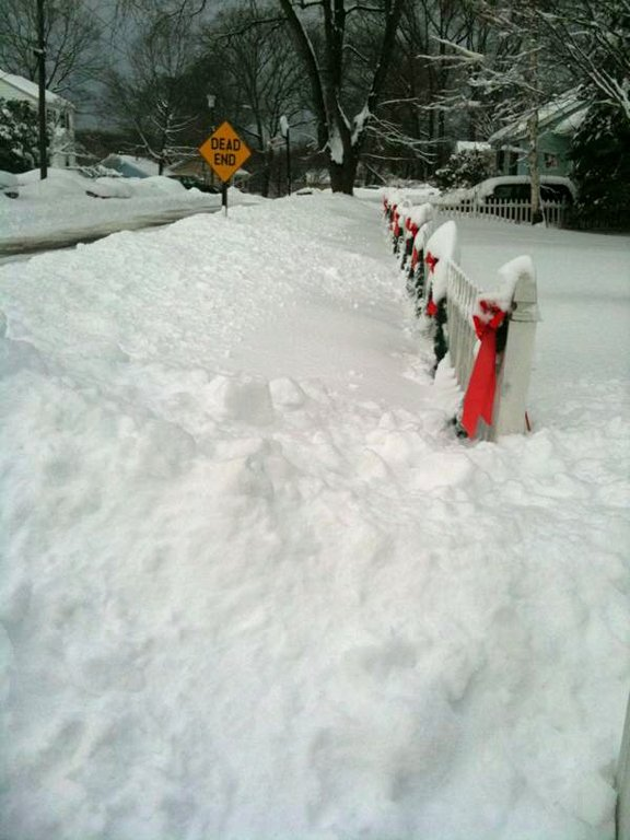 Snow piled up against a white picket fence