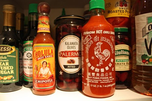 Bottles of hot sauce, vinegars and condiments