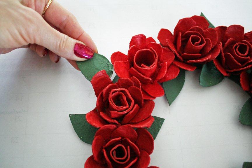 Hot gluing the last green leaf onto the frame of an egg carton rose wreath