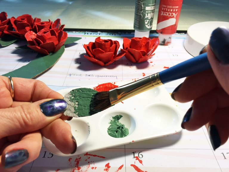 Painting the leaves of an egg carton rose