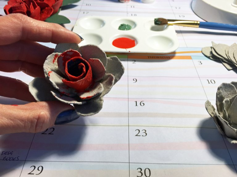 Painting an egg carton rose with red acrylic paint