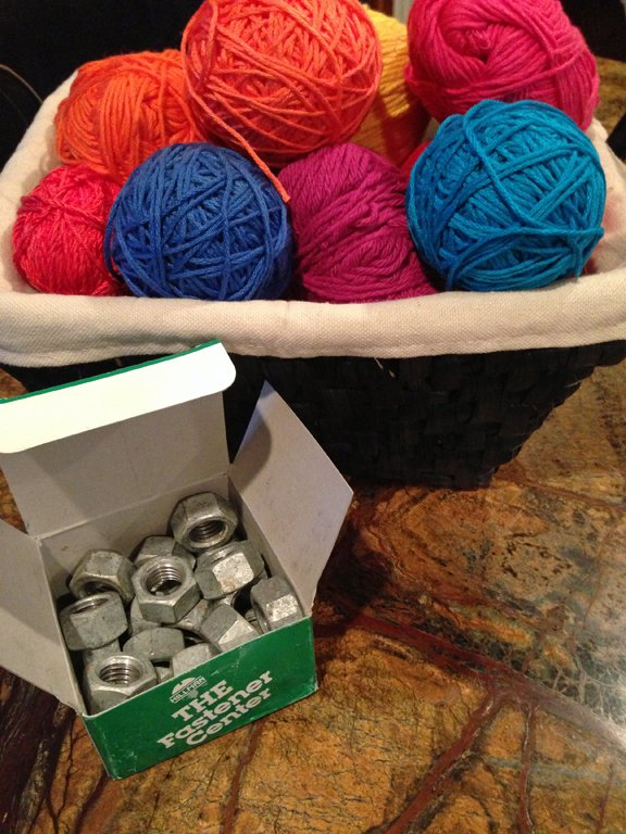 Yarns in a basket and a contractor's box of hex nuts used to make pattern weights for sewing