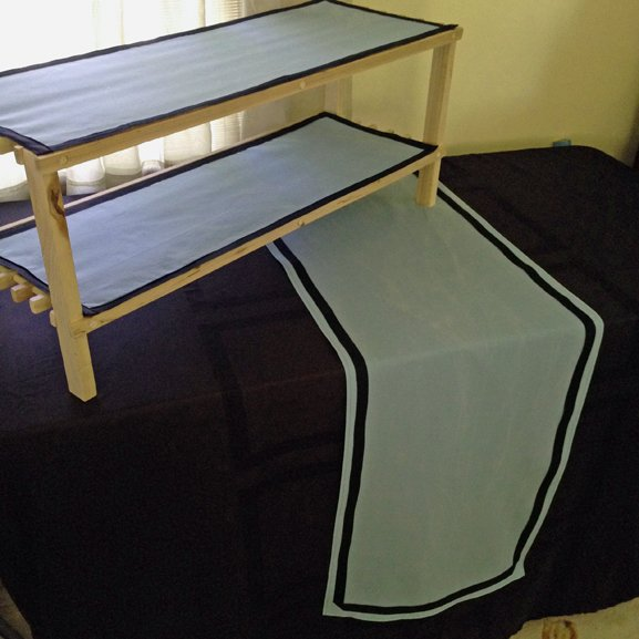 Double shelf for table top, covered in a custom-made black tablecloth with custom aqua runners