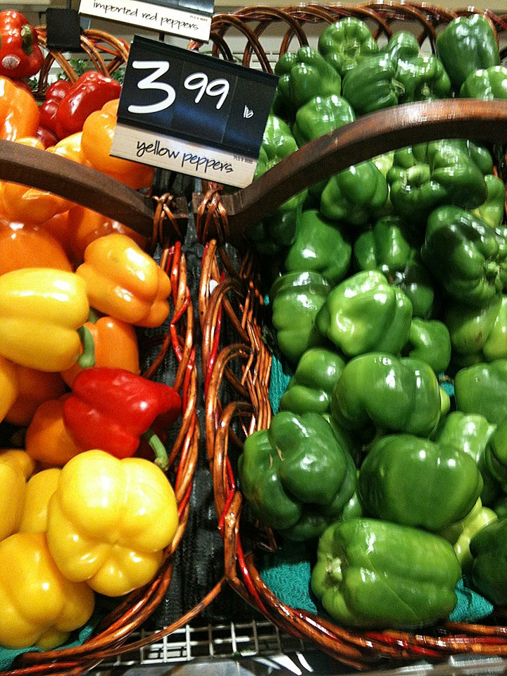 Several varieties of bell peppers on display in the grocery store